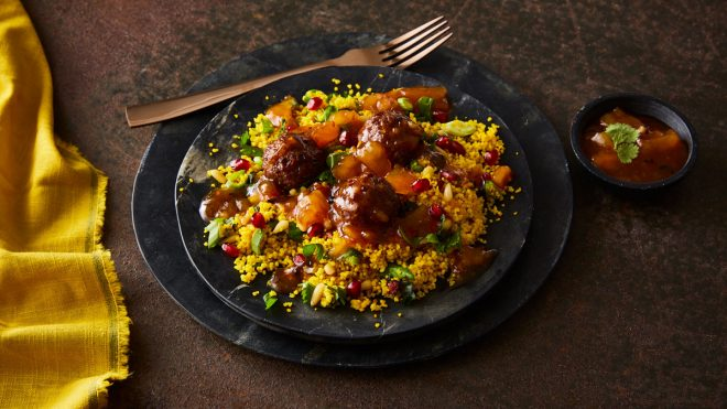 Lebanese Lamb Meatballs served on a bed of couscous on two black serving plates