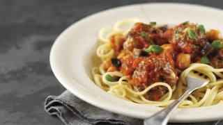 Greek Lamb Meatballs served on top of linguine in a white bowl with a fork