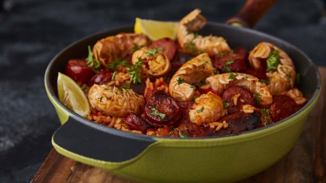 Sausage, Chorizo and Langoustine Jambalaya served in a gree skillet on top of a wooden board