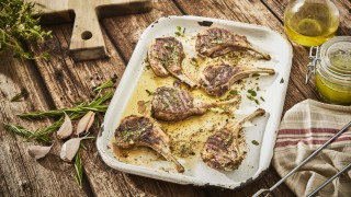 Super Easy Herb Marinated Lamb Chops served on a baking tray with sprigs on rosemary and olive oil