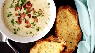 Stilton and Bacon Soup with Cheese and Garlic Slices served in a white bowl next to a blue tablecloth