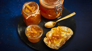 Seville Orange Marmalade with Gin spread on buttered bread and stored in a glass jar