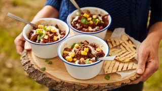 Mexican Mole Chilli served in dishes, on top of a wooden board with grilled tortillas