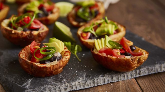 Mexican Style Mini Potato Skins (Vegan) served on a slate and topped with spring onions