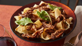 Mulled Spiced Beef Ragu served in a red bowl and topped with leafy greens