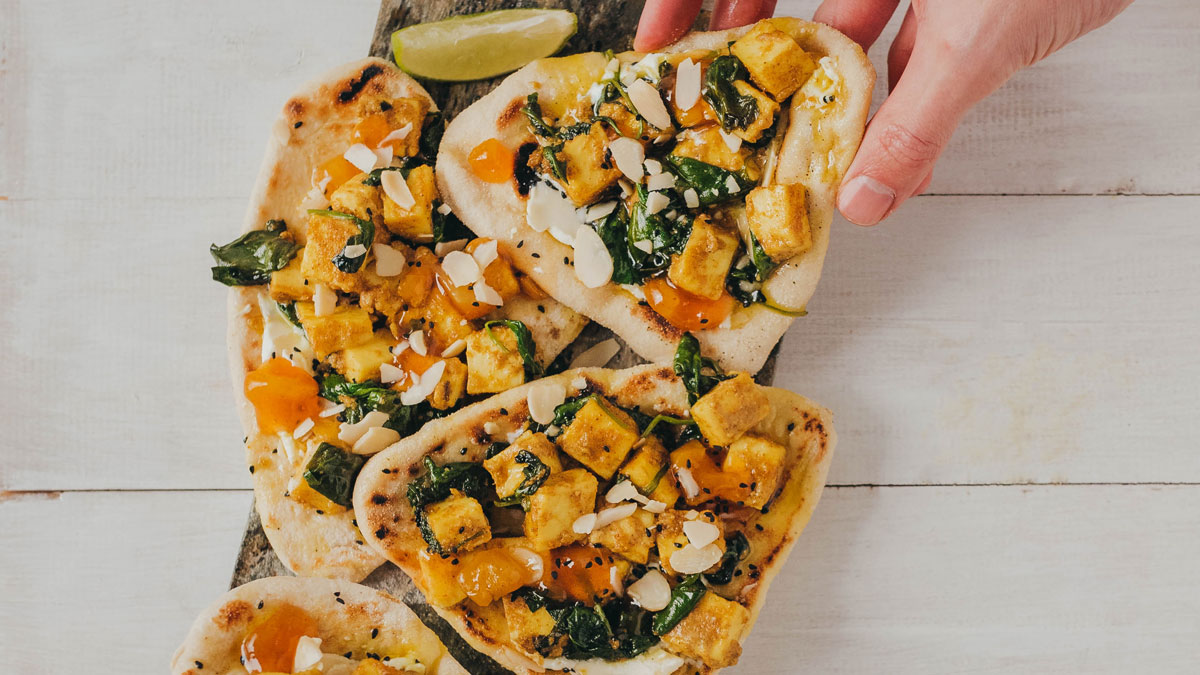 Lightly Spiced Paneer Flatbreads served with a lime wedge on a wooden board