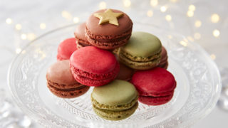Festive Macaron Trio, served on a glass cake dish, piled on top of one another and topped with a gold star
