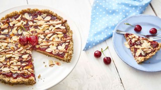 No Bake Cherry Bakewell served on a white dish, with a sliced removed and to the side on a blue plate