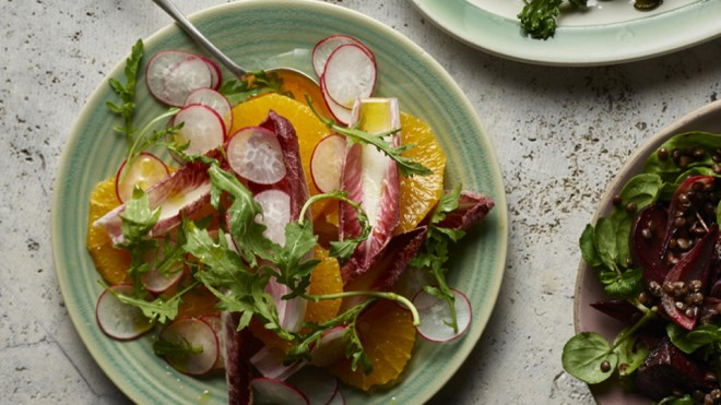 Orange, Red Chicory and Radish Salad served on a green plate topped with rocket