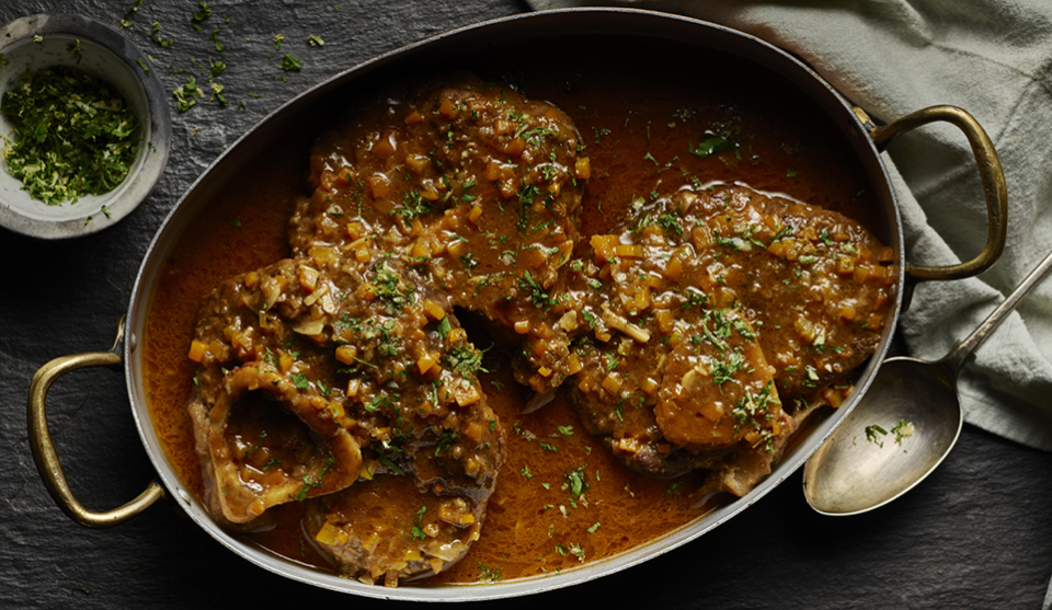 Ossobuco served in a metal casserole dish topped with parsley