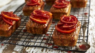Blood Orange and Poppy Seed Loaves served on a cooling rack drizzled with the syrup