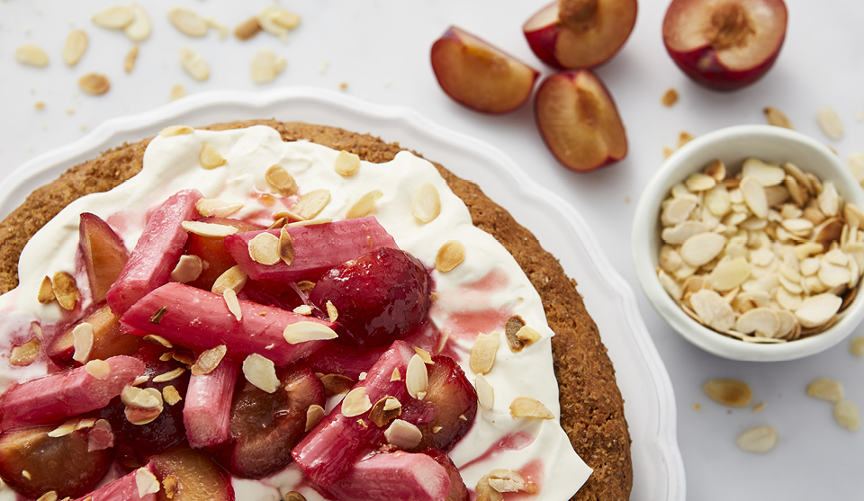 Almond, Plum and Rhubarb Cake topped with flaked almonds, next to a bowl of almonds and sliced plums