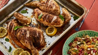 Persian Spatchcock Chicken served in a roasting tray with lemon wedges and a side dish of cous cous salad