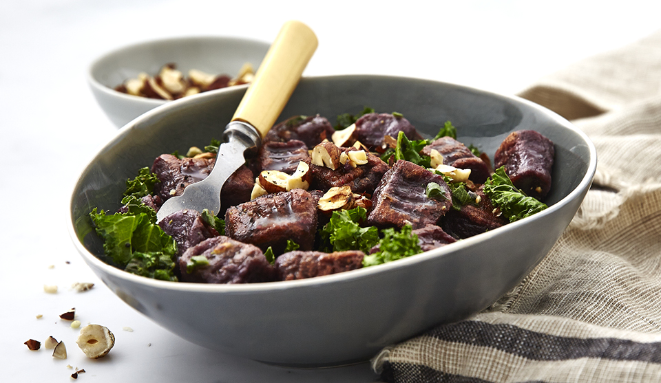 Purple Sweet Potato Gnocchi served in a grey bowl topped with chopped hazelnuts