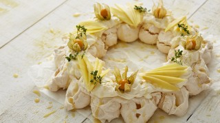 Coconut Meringue Wreath served on baking parchment and drizzled with lemon curd