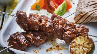 Brazilian Churrasco Beef Kebabs served on a white plate with coloured tomato salad