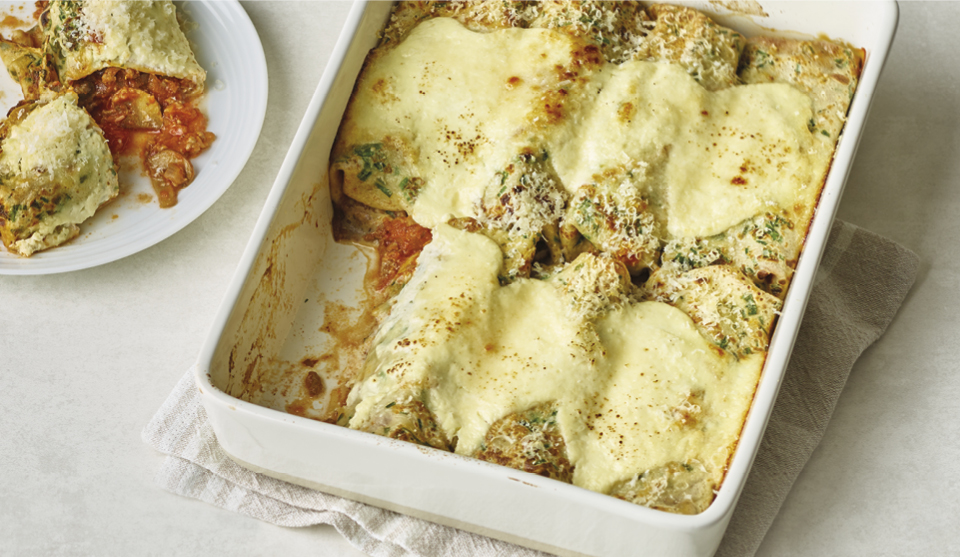 Beef Ragu Pancake Cannelloni served in a casserole dish, with a portion placed on a plate to the left, cut open to see the filling