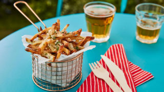 Parmesan and truffle fries served in a basket with wooden cutlery