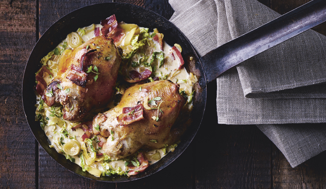Partridge with cider and savoy cabbage served in a metal pan on top of a grey cloth