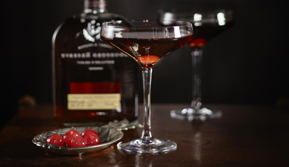 The Perfect Manhattan served in two glasses next to a dish of maraschino cherries