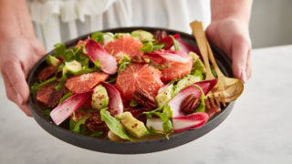 Pink Grapefruit, Candied Pecan and Avocado Sald served in a grey bowl with a gold fork and spoon