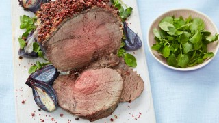 Roast Topside of Beef with Pink Peppercorn Crust served sliced on a white board