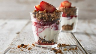 Poached Plums with Quinoa Granola served in glasses with granola scattered around the glasses