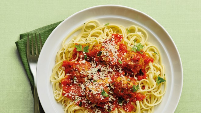 Herby Pork Meatballs with Linguine, served on a white plate, topped with parsley and Parmesan cheese