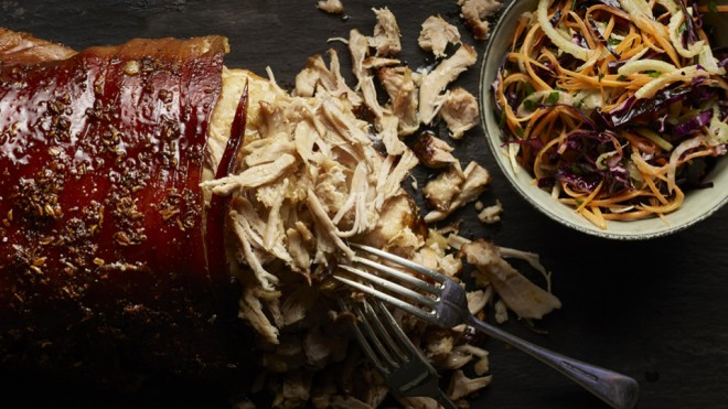 Pulled Pork which has been shredded by two forks next to a bowl of crunchy coleslaw