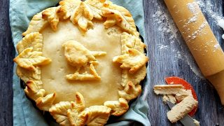 Apple and Pumpkin Spice Cheese Pie served on a blue tablecloth with a pastry bird and leaves on top