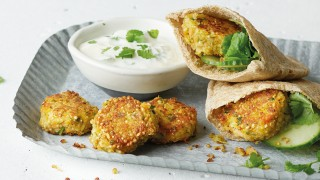 Spiced Quinoa Falafel served in pitta breads on a blue dish with a lemon and yoghurt sauce