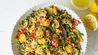 Quinoa, Roasted Vegetable and Puy Lentil Salad served in a white bowl, with sprinkled parsley and squeezed lemon wedges to the side