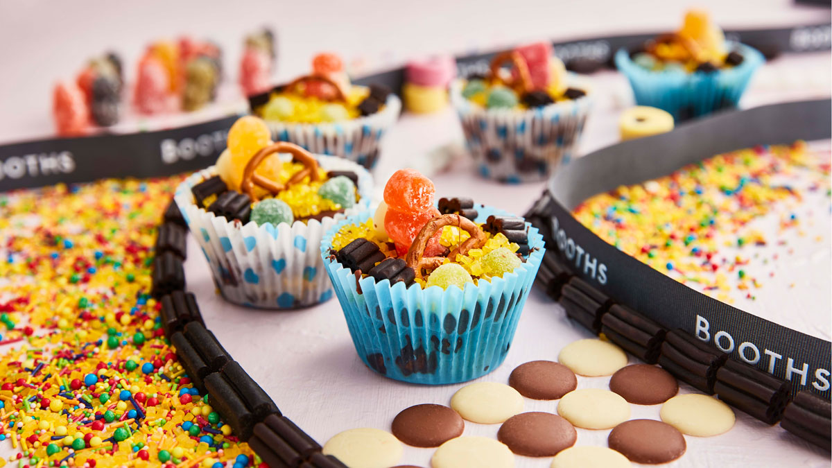 Chocolate Tiffin Race Cars surrounded by sprinkles and chocolate buttons