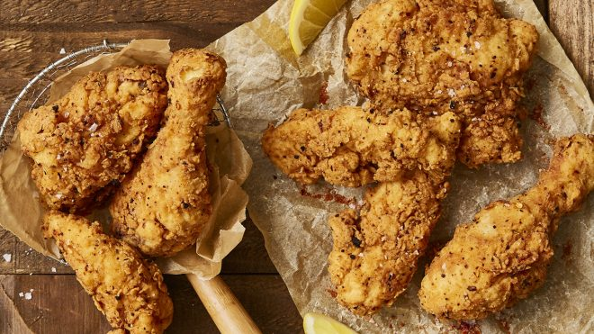 Southern Fried Chicken served on baking parchment with wedges of lemon