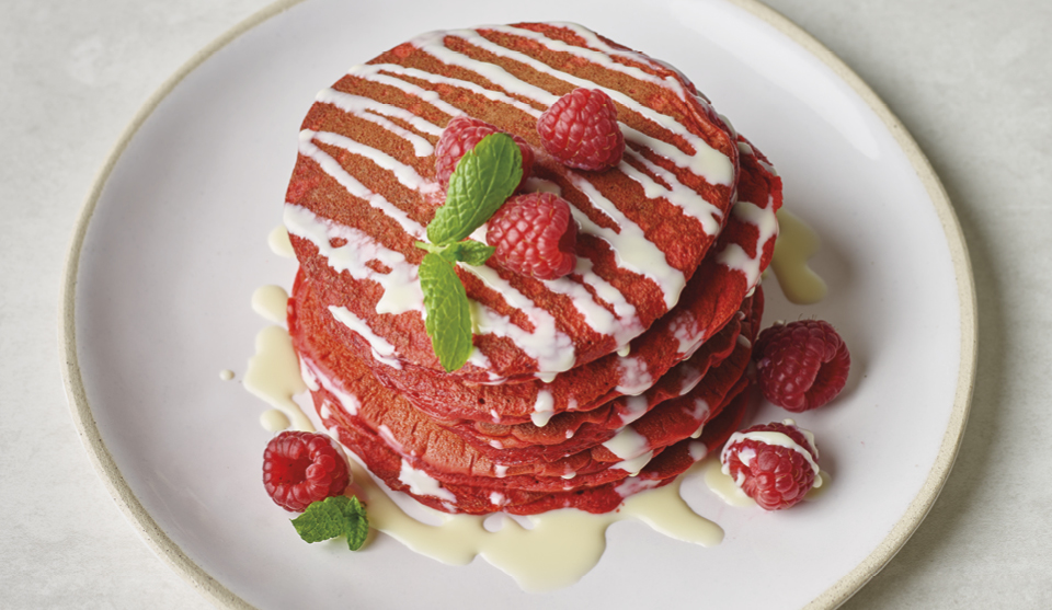 Red Velvet Pancakes with White Chocolate Sauce served on a white plate and topped with raspberries