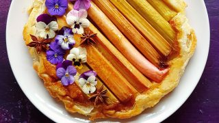 Autumn Spiced Rhubarb Tarte Tatin served on a white plate topped with edible flowers and star anise