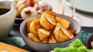 A bowl of roast potatoes in a blue and white bowl