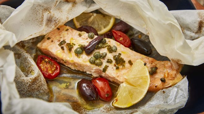 Salmon en Papillote served with olives, tomatoes and a wedge of lime