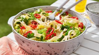 Savoy Cabbage, Red Chilli and Lemon Oil Pasta served in a in a white bowl with two forks