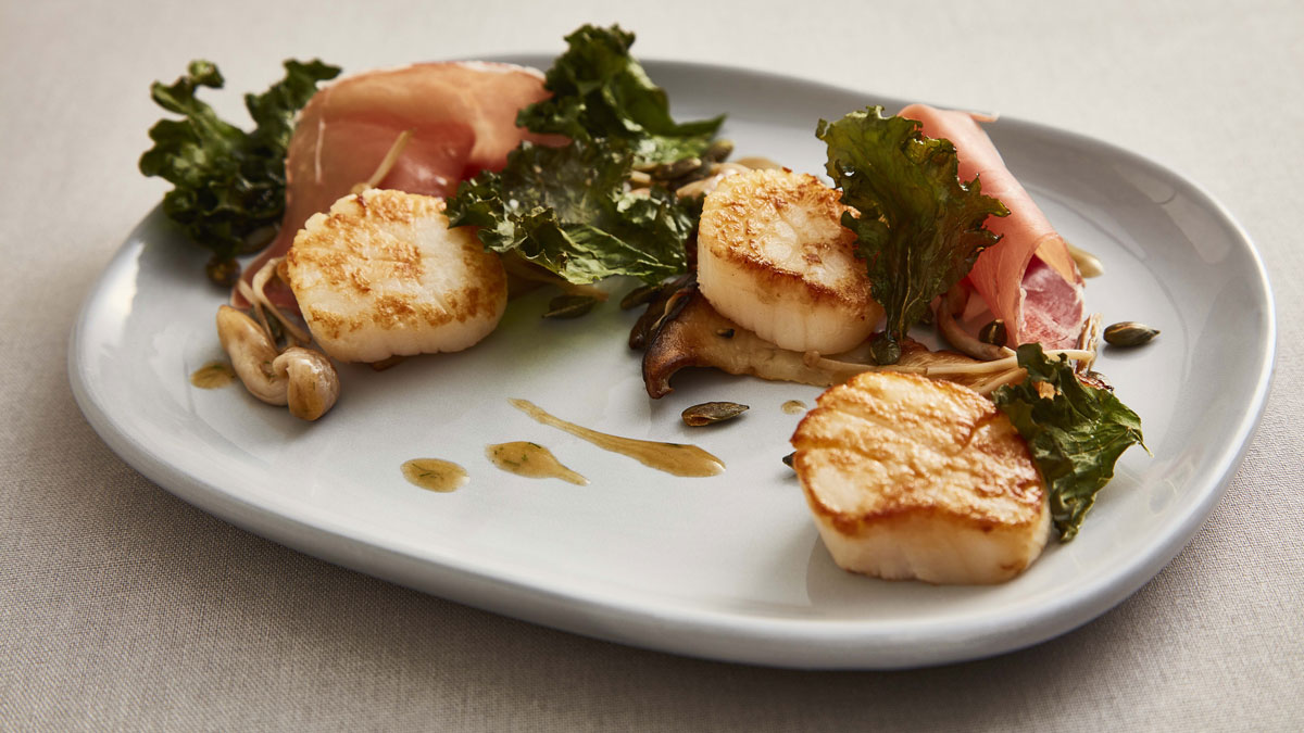 Scallops, Air-Dried Ham and Wild Mushrooms serve on a white plate with kale and olive oil