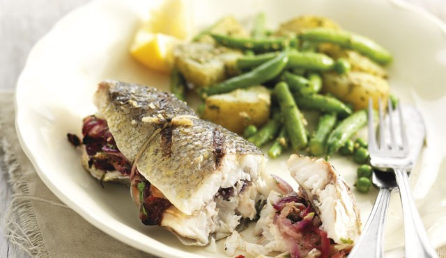 Sea Bass Filled with Fennel, Chilli and Lemon with Summer Vegetables served on a white plate with green beans and new potatoes
