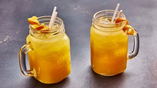 Sicillian Sunset Cocktail served in glass jars, with orange peel garnish
