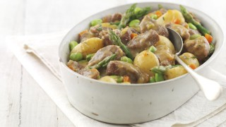 New Season Lamb served in a white casserole dish with asparagus, new potatoes and carrot