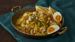 Smoked Haddock Kedgeree served in a small skillet on top of a blue tablecloth
