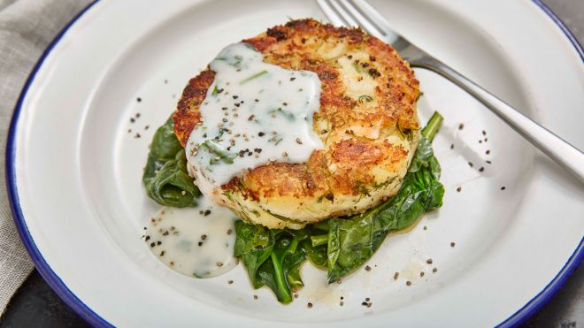 Smoked Salmon Hash Browns with Parsley Sauce served on a bed of spinach in a white dish