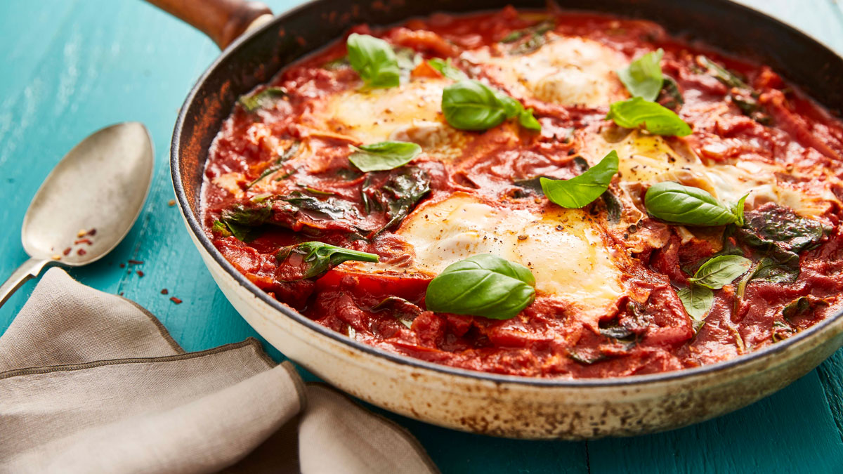 Smoky Baked Eggs served in a pan sprinkled with spinach