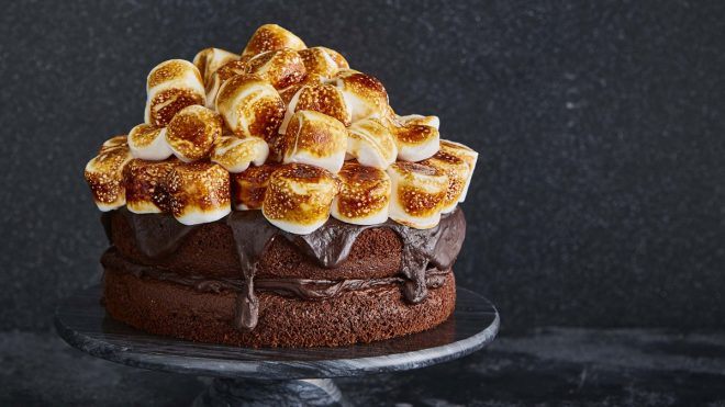 Smores Chocolate Cake served ona black cake dish, with toasted marshmallows on top