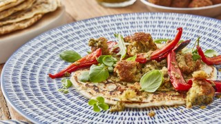 Spelt Pancakes with Falafels on a blue and white plate, topped with roasted red peppers and basil