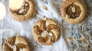 Four Spiced Caramel Clementine and Frangipane Tarts topped with flaked almonds