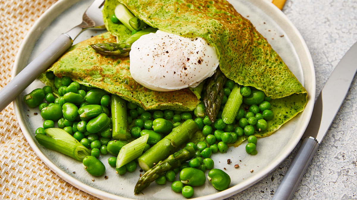 Spinach Blender Crepes served on a white plate, with spring greens and a poached egg